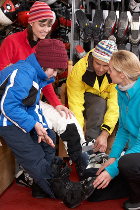 Sales Assistant Helping Family To Try On Ski Boots In Hire Shop